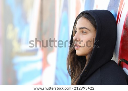 Profile portrait of a skater style teenager girl with an unfocused graffiti wall in the background - stock photo