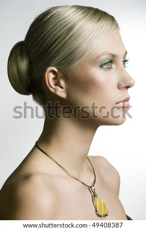 profile portrait of a young and cute woman with hair stylish and a yellow nacklace - stock photo