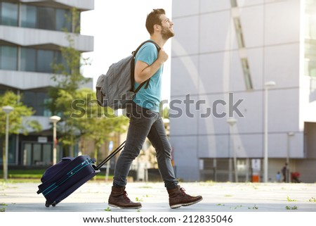 Profile portrait of a young man walking with suitcase and bag - stock photo