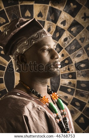Profile portrait of an African American man wearing traditional African clothing, in front of a patterned wall. Vertical format. - stock photo