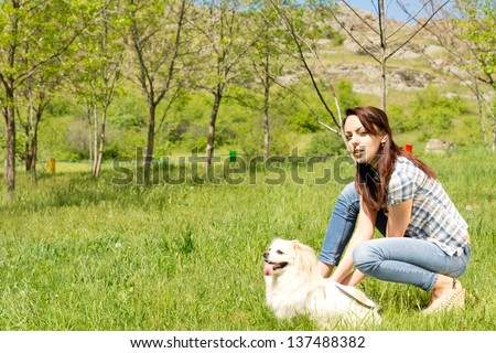 Profile portrait of an attractive young woman and her adorable little fluffy dog posing together in long green grass in a rural landscape - stock photo