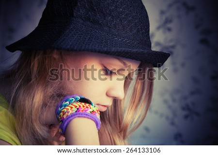 Profile portrait of beautiful blond teenage girl in black hat and rubber loom bracelets, vintage dark toned photo, instagram style effect - stock photo