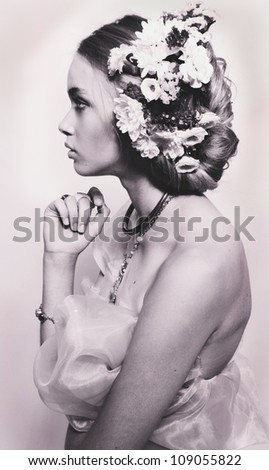 Profile portrait of beautiful teenage girl with flowers in hairstyle and jewelery isolated - stock photo