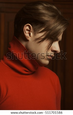 Profile portrait of handsome young man in terracotta color turtleneck pullover. Blond healthy glossy hair. Close up. Indoor shot