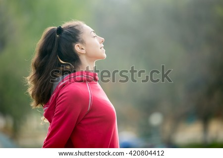 Profile portrait of happy sporty woman relaxing in park. Female model relaxing, breathing fresh air outdoors. Healthy active lifestyle concept. Copy space - stock photo