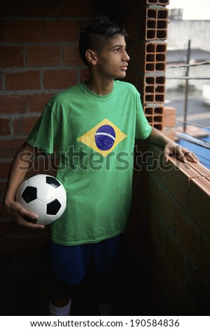 Profile portrait of serious Brazilian young man wearing Brazil flag t-shirt standing holding soccer ball looking out the favela window - stock photo