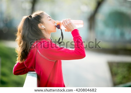 Profile portrait of sporty woman drinking in park after jogging. Female athlete runner getting ready for running routine. Fit girl listening music and enjoying drink with closed eyes outdoors - stock photo