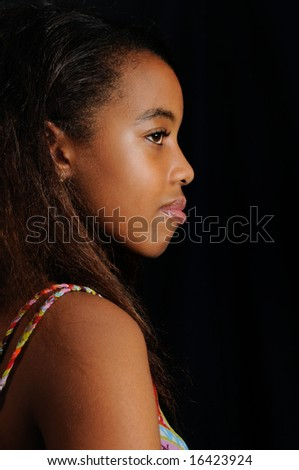 Profile portrait of young african girl isolated on black - stock photo