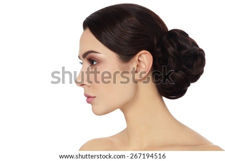 Profile portrait of young beautiful woman with stylish hair bun over white background, copy space - stock photo