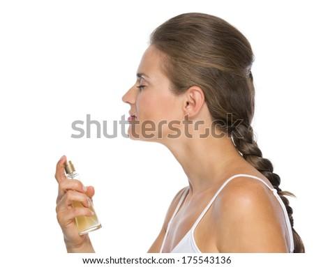 Profile portrait of young woman applying perfume - stock photo