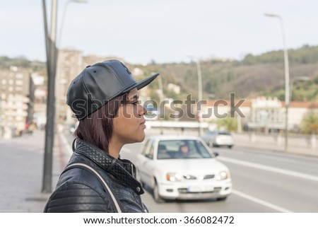 Profile portrait of young woman with baseball cap in the street.