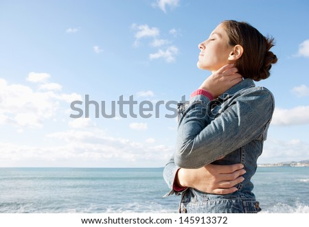 Profile portrait view of a young woman facing the sea and breathing fresh air with her eyes closed against an intense blue color sky during a sunny day. - stock photo
