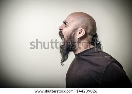 profile screaming angry bearded man on gray background - stock photo