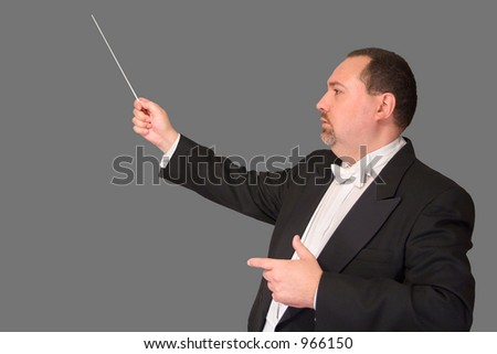 Profile shot of a conductor with his baton in concert dress, isolated against gray background.