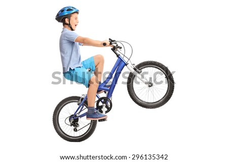 Profile shot of a little boy with blue helmet doing a wheelie on a small blue bike isolated on white background - stock photo