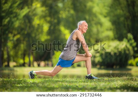 Profile shot of a senior in sportswear doing stretching exercises in a park and listening to music on headphones - stock photo