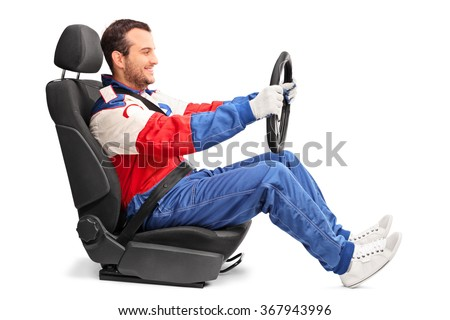 Profile shot of a young car racer holding a steering wheel and pretending to drive isolated on white background - stock photo