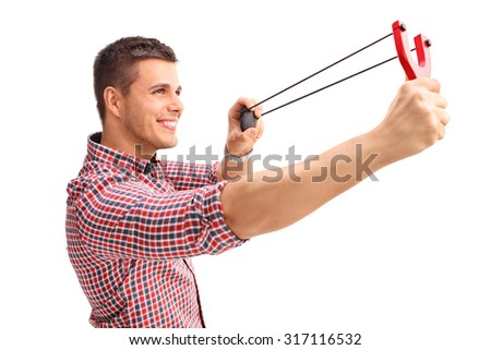 Profile shot of a young cheerful man shooting a slingshot and smiling isolated on white background - stock photo