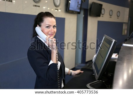 Profile shot of attractive executives at the reception of a hotel. Woman attending phone call - stock photo