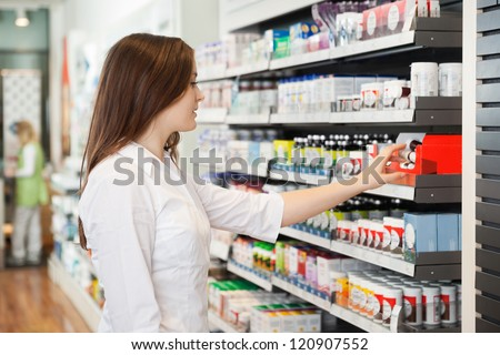 Profile shot of beautiful young woman shopping at pharmacy - stock photo