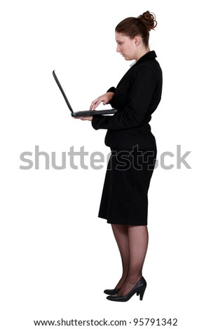 Profile shot of brunette with laptop - stock photo