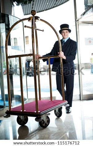 Profile shot of doorman holding cart at the entrance of hotel - stock photo
