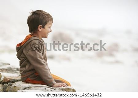 Profile shot of little boy sitting on wall at beach - stock photo