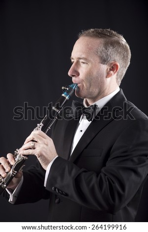 Profile shot of man in tuxedo playing clarinet over black background - stock photo