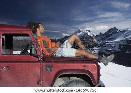 Profile shot of man relaxing on car hood against mountains during winter - stock photo