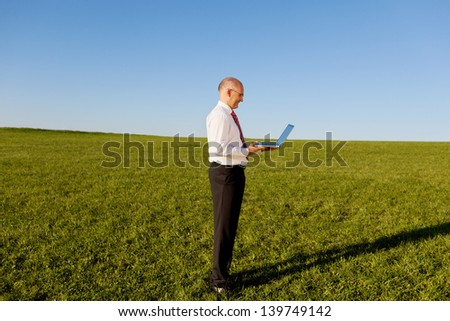 Profile shot of mature businessman holding laptop on grassy field against clear sky - stock photo