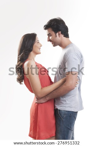 Profile shot of smiling couple embracing against white background - stock photo