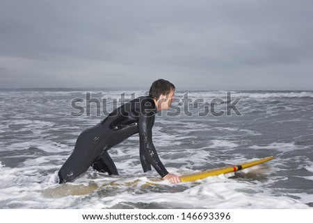 Profile shot of young man in wetsuit surfing at beach - stock photo