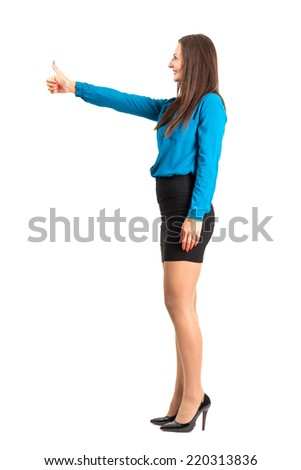 Profile side view of business woman with thumbs up gesture. Full body length isolated over white background. - stock photo