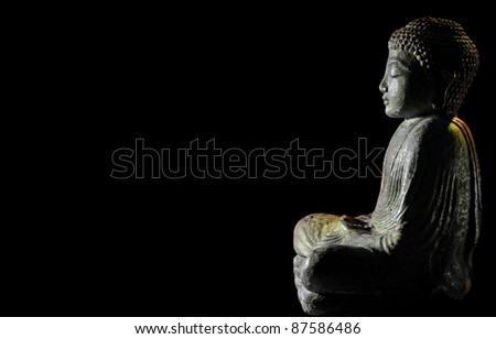 profile silhouette of Buddha with black background - stock photo