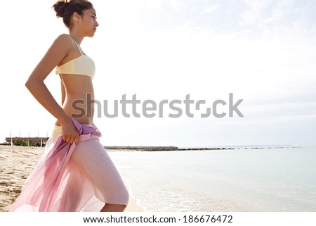 Profile view of a beautiful young woman body wrapping a silk fabric sarong around her body and contemplating the blue sea and sky during a sunny day on holiday. Travel and beauty lifestyle. - stock photo