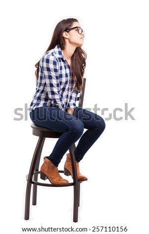 Profile view of a cute hipster girl sitting on a chair and looking towards copy space - stock photo