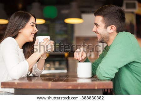 Profile view of a good looking young couple drinking coffee and having fun at a restaurant - stock photo