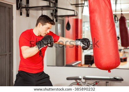 Profile view of a good looking young Hispanic man practicing box on a punching bag at the gym - stock photo