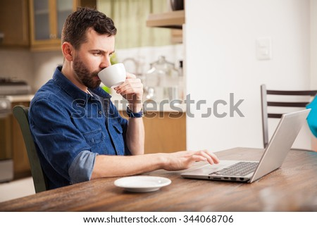 Profile view of a handsome man with a beard drinking some coffee and using a laptop computer at home - stock photo