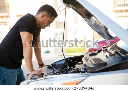 Profile view of a handsome young Hispanic man looking at a car with its hood open, trying to fix it - stock photo