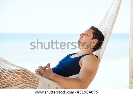 Profile view of a handsome young man taking a nap and sleeping in a hammock at the beach - stock photo