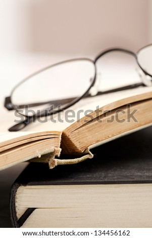 Profile view of a pair of reading glasses laying on top of some old hard back books on a desk.