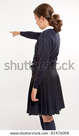 Profile view of  a schoolgirl pointing at something, isolated in white - stock photo