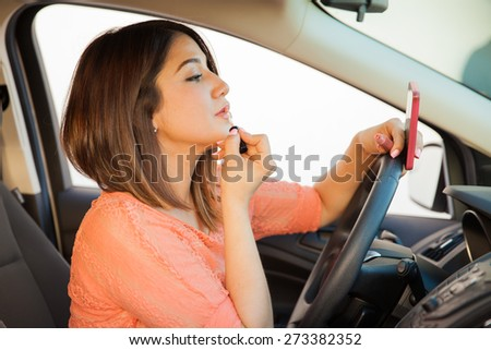 Profile view of a young brunette putting some lipstick on and looking at her cell phone while driving a car - stock photo