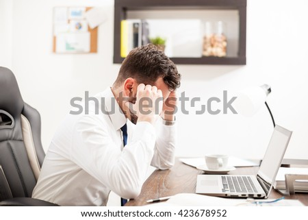 Profile view of a young businessman feeling overwhelmed and frustrated at work in his office - stock photo