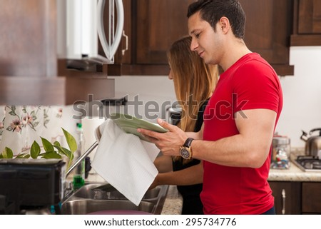 Profile view of a young couple washing and drying the dishes together at home - stock photo
