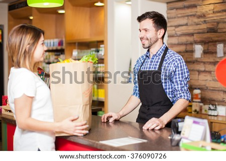 Profile view of a young male cashier helping a customer pay for all her groceries at a store - stock photo
