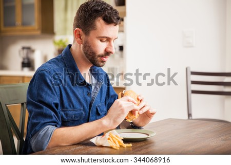 Profile view of a young man enjoying a hamburger with fries at home - stock photo