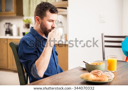Profile view of a young man in a denim shirt drinking coffee and eating breakfast at home - stock photo