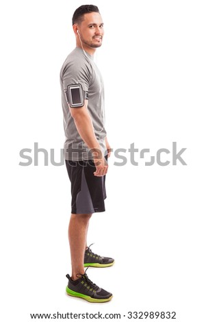 Profile view of a young man wearing earbuds and an armband standing ready to exercise - stock photo